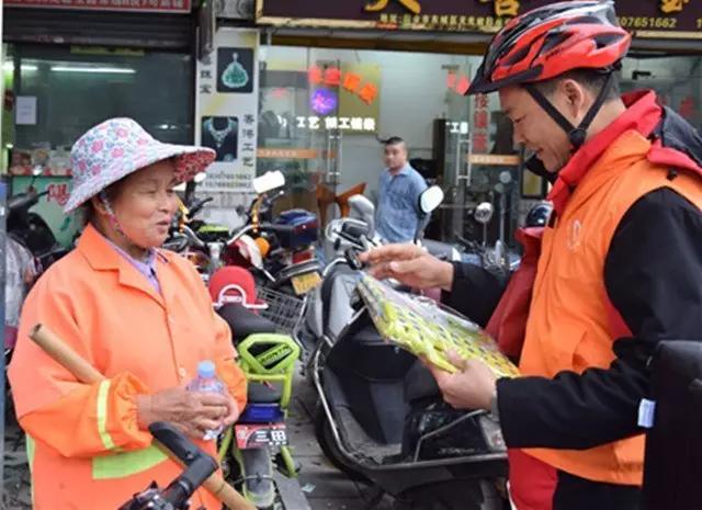 志愿者为环卫工人送上爱心水和折迭凳子。图片来源:四会文明网.png